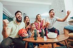 Gelukkige vrienden of basketbalventilators die basketbal op spel op TV letten Stock Foto's