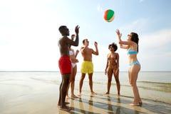 Gelukkige vrienden die bal op de zomerstrand spelen royalty-vrije stock foto