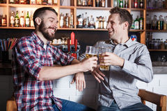 Gelukkige vrienden die bier drinken bij teller in bar Stock Afbeeldingen