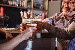 Gelukkige vrienden die bier drinken bij teller in bar Stock Fotografie