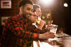 Gelukkige vrienden die bier drinken bij teller in bar Royalty-vrije Stock Foto's