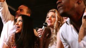 Gelukkige vrienden die bij de karaoke in nachtclub zingen stock videobeelden