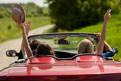 Gelukkige vrienden die in cabriolet auto bij land drijven royalty-vrije stock foto
