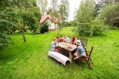 Gelukkige vrienden die diner hebben bij de partij van de de zomertuin stock afbeeldingen