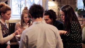 Gelukkige vrienden die en bij restaurant eten drinken stock videobeelden