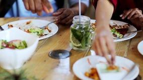Gelukkige vrienden die en bij restaurant eten spreken stock videobeelden