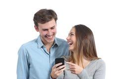 Gelukkige vrienden die en op een slimme telefoon letten lachen Stock Afbeeldingen