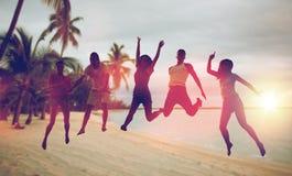 Gelukkige vrienden die en op strand dansen springen stock fotografie