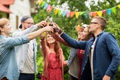 Gelukkige vrienden die glazen clinking bij de zomertuin Stock Afbeeldingen