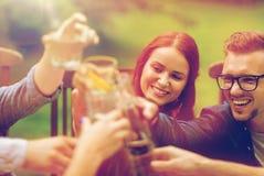 Gelukkige vrienden die glazen clinking bij de zomertuin Stock Fotografie