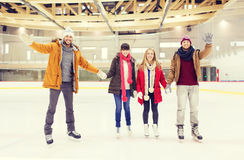 Gelukkige vrienden die handen op het schaatsen piste golven Royalty-vrije Stock Fotografie