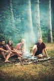 Gelukkige vrienden die kampvuur in het avond, vriendschaps en vrije tijdsconcept rondhangen Jonge glimlachende paren die hebben royalty-vrije stock foto