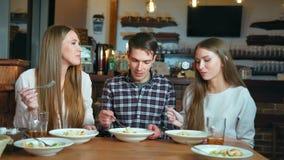 Gelukkige vrienden die in koffie zitten terwijl het eten van en het drinken van alcohol stock videobeelden