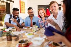 Gelukkige vrienden die met geld rekening betalen bij restaurant stock fotografie