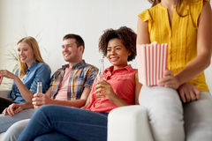 Gelukkige vrienden die met popcorn op TV thuis letten Stock Fotografie