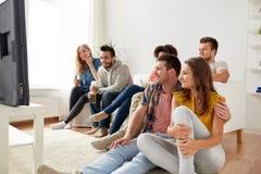 Gelukkige vrienden die met popcorn op TV thuis letten Stock Foto's