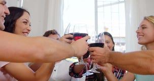 Gelukkige vrienden die met rode wijn toejuichen stock video