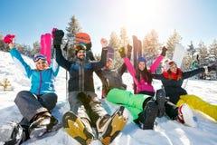 Gelukkige vrienden die op berg op de winterdag genieten van Stock Foto's