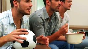 Gelukkige vrienden die op een voetbalwedstrijd letten stock videobeelden