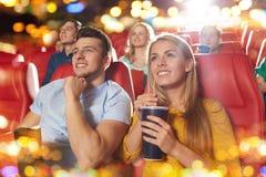 Gelukkige vrienden die op film in theater letten royalty-vrije stock fotografie