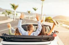 Gelukkige vrienden die pret in convertibele auto hebben bij zonsondergang in vakantie - Jongeren die partij maken en in een cabri royalty-vrije stock fotografie