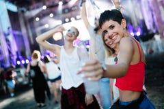 Gelukkige vrienden die pret hebben bij muziekfestival royalty-vrije stock afbeeldingen
