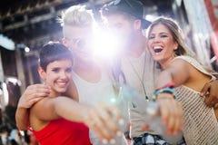 Gelukkige vrienden die pret hebben bij muziekfestival stock afbeelding