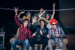 Gelukkige vrienden die pret met kostuums in een partij hebben stock afbeelding