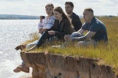Gelukkige vrienden die pret op de heuvel over de rivier hebben die van recreatie en het spreken genieten stock foto's