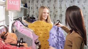 Gelukkige vrienden die samen in de wandelgalerij winkelen Twee meisjes bij de opslag stock videobeelden