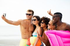 Gelukkige vrienden die selfie op de zomerstrand nemen stock afbeelding