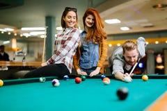 Gelukkige vrienden die spelend pool genieten van royalty-vrije stock afbeeldingen