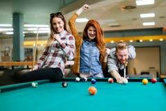 Gelukkige vrienden die spelend pool genieten van stock foto