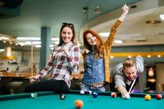 Gelukkige vrienden die spelend pool genieten van stock foto's