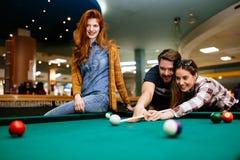 Gelukkige vrienden die spelend pool genieten van royalty-vrije stock afbeelding