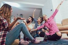 Gelukkige vrienden die spelgissing spelen die en pret hebben stock afbeelding