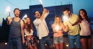 Gelukkige vrienden die sterretjes aansteken en van vrijheid genieten royalty-vrije stock foto's