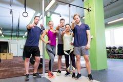 Gelukkige vrienden die vingers op u in gymnastiek richten Stock Foto
