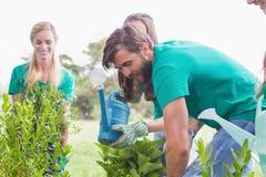 Gelukkige vrienden die voor de gemeenschap tuinieren Stock Foto