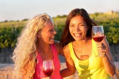 Gelukkige vrienden die wijn het lachen drinken Royalty-vrije Stock Afbeeldingen