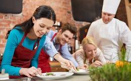 Gelukkige vrienden en het mannelijke chef-kok koken in keuken Stock Afbeeldingen