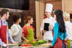 Gelukkige vrienden met chef-kok en tabletpc in keuken Royalty-vrije Stock Foto