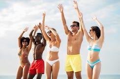 Gelukkige vrienden met handen omhoog op de zomerstrand stock foto