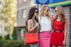 Gelukkige vrienden met het winkelen zakken klaar aan het winkelen Stock Afbeelding