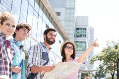 Gelukkige vrienden met wegenkaart met vrouw het richten weg in stad Royalty-vrije Stock Afbeeldingen