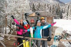 Gelukkige vrienden op koude de winterdag bij bergplattelandshuisje en het hebben Stock Foto
