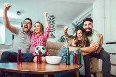 Gelukkige vrienden of voetbalventilators die op voetbal op TV letten stock afbeeldingen