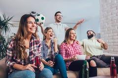 Gelukkige vrienden of voetbalventilators die op voetbal op TV letten stock foto's