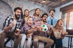 Gelukkige vrienden of voetbalventilators die op voetbal op TV letten en overwinning vieren stock foto's