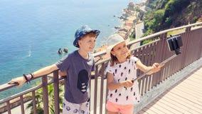 Gelukkige vriendenjonge geitjes die selfie in mooie stad van Scilla Italy, glimlachende kinderen nemen die pret hebben die samen  stock fotografie